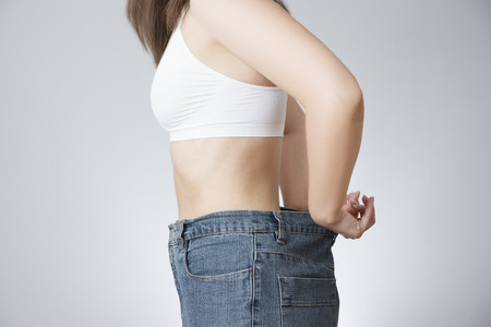 large size: The concept of weight loss. Beautiful slender female body. Young woman in jeans large size. Stock Photo