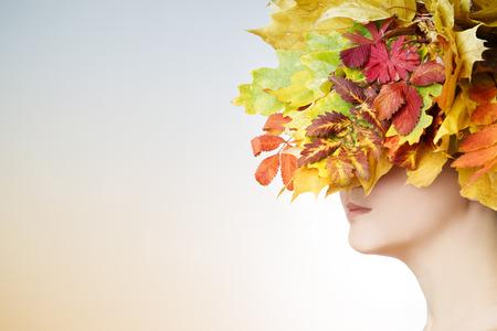 style: Bella donna giovane con autunno giallo corona su sfondo luminoso