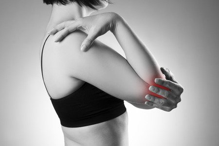 Woman with pain in elbow. Pain in the human body. Black and white photo with red dot