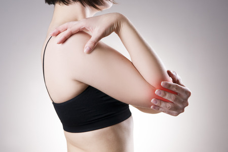 enhanced: Woman with pain in elbow. Pain in the human body on a gray background with red dot