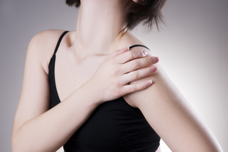 肩の痛みを持つ女性。灰色の背景に人間の体の痛み