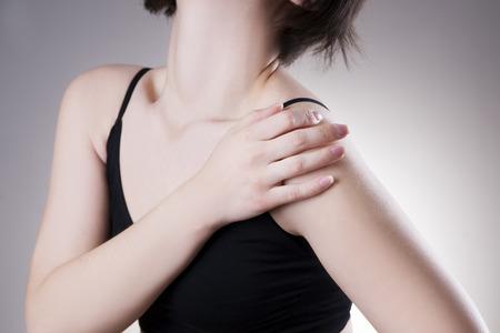 어깨에 통증을 가진 여자입니다. 회색 배경에 인간의 몸에 통증 스톡 콘텐츠
