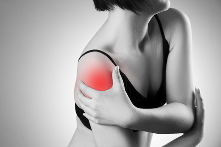 Woman with pain in shoulder. Pain in the human body. Black and white photo with red dot