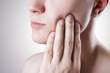 Mann mit Zahnschmerzen. Schmerzen in den menschlichen Körper auf einem grauen Hintergrund Standard-Bild