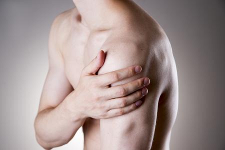 hombros: Hombre con dolor en el hombro. El dolor en el cuerpo humano sobre un fondo gris
