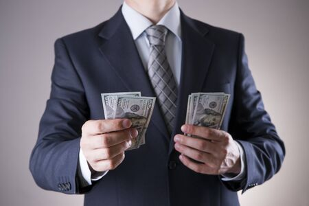 corruptible: Businessman with money in studio on a gray background. Corruption concept. Hundred dollar bills
