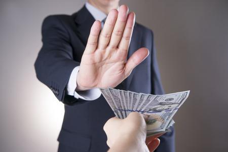 Geschäftsmann mit Geld im Studio auf einem grauen Hintergrund. Korruption Konzept. Hundert Dollar-Scheine