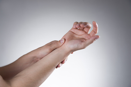 carpal tunnel: Pain in the joints of the hands on a gray background. Carpal tunnel syndrome. Care of male hands