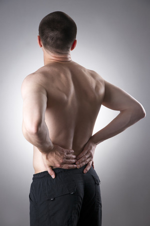 Kidney pain. Man with backache. Pain in the mans body on a gray background Stock Photo