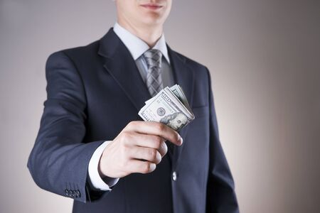 venality: Businessman with money in studio on a gray background. Corruption concept. Hundred dollar bills