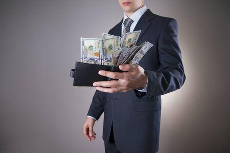 money cash: Hombre de negocios con el dinero en el estudio sobre un fondo gris. Concepto de la corrupci�n