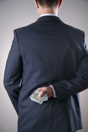 levy: Businessman with money in studio on a gray background. Corruption concept. Hundred dollar bills