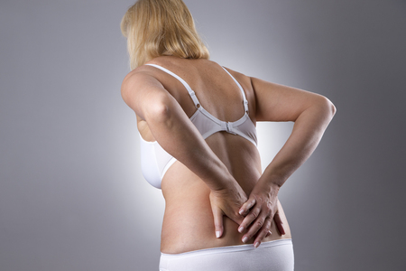 chronic pain: Woman with backache. Pain in the  human body on a gray background
