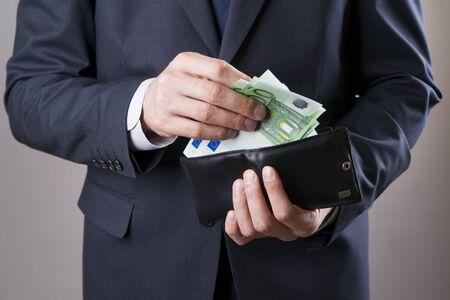 Hombre de negocios con el dinero en el estudio sobre un fondo gris. Concepto de la corrupción