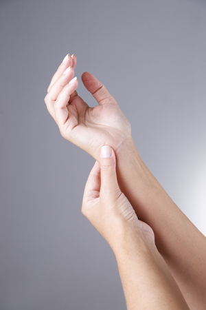holding arm: Pain in the joints of the hands on a gray background. Carpal tunnel syndrome. Care of male hands