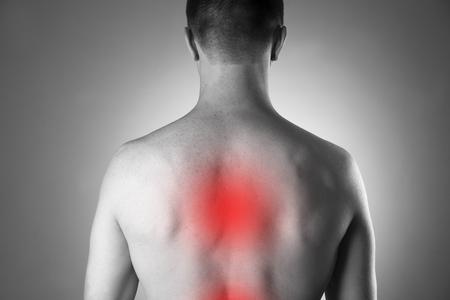 背中の痛みを持つ男。人間の体の痛み。赤のドットの黒と白の写真