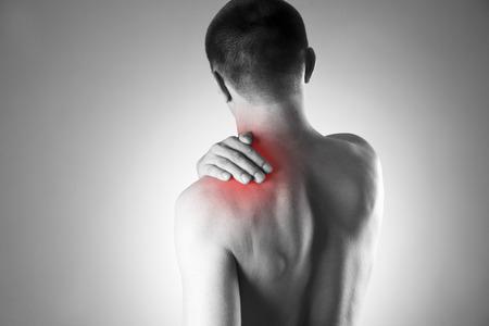 hombros: Hombre con dolor en el hombro. El dolor en el cuerpo humano. Foto en blanco y negro con el punto rojo
