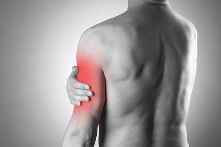 dolor espalda: Hombre con dolor en el hombro. El dolor en el cuerpo humano. Foto en blanco y negro con el punto rojo