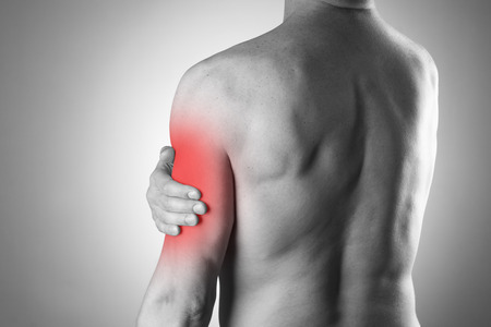 pain: Man with pain in shoulder. Pain in the human body. Black and white photo with red dot