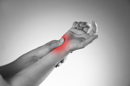 arthritis: Pain in the joints of the hands. Carpal tunnel syndrome. Black and white photo with red dot