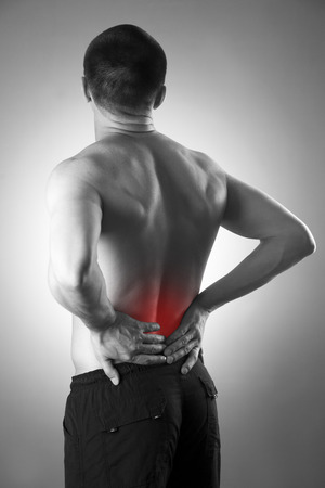 lower back pain: Man with backache. Pain in the human body. Black and white photo with red dot