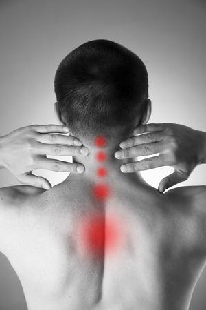 dolor espalda: Dolor en el cuello. Hombre con dolor de espalda. Dolor en el cuerpo del hombre. Foto en blanco y negro con el punto rojo