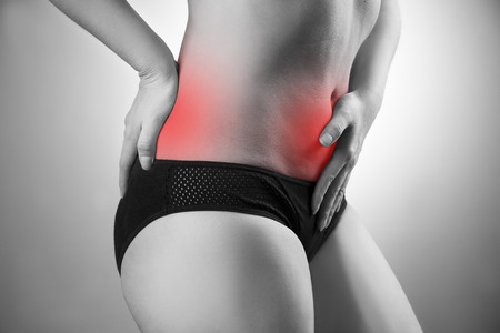 Woman with abdominal and back pain. Pain in the human body. Black and white photo with red dot