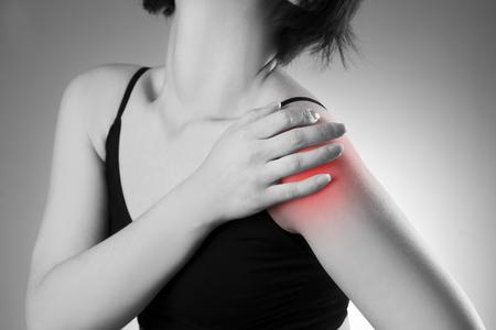 dolor: Mujer con dolor en el hombro. El dolor en el cuerpo humano. Foto en blanco y negro con el punto rojo Foto de archivo