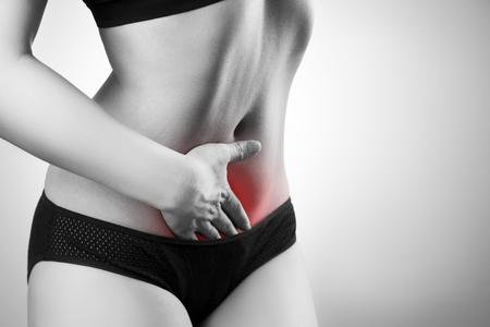abdominal pain: Mujer con dolor abdominal. El dolor en el cuerpo humano. Foto en blanco y negro con el punto rojo Foto de archivo