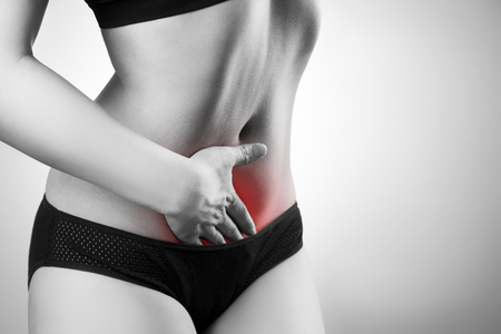 Woman with abdominal pain. Pain in the human body. Black and white photo with red dot Stock Photo