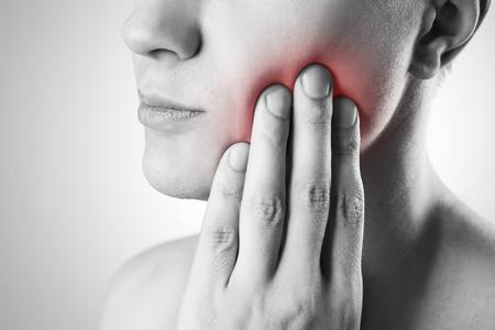 dientes: Hombre con un dolor de muelas. El dolor en el cuerpo humano. Foto en blanco y negro con el punto rojo Foto de archivo