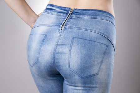 nude female buttocks: Woman in jeans close up. Beautiful female hips and buttocks on a gray background