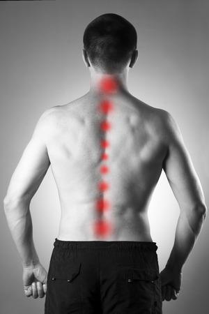 dolor: Hombre con dolor de espalda. El dolor en el cuerpo humano. Foto en blanco y negro con el punto rojo
