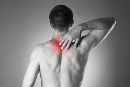 Man with backache. Pain in the human body. Black and white photo with red dot