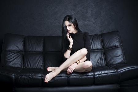 Schöne junge Frau mit langen Beinen im Bodysuit sitzt auf einem schwarzen Sofa