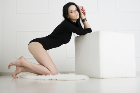 Beautiful young woman with long legs in bodysuit with white cube on the floor