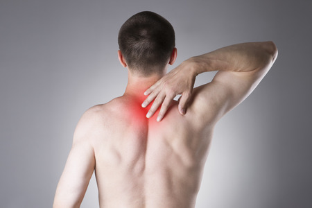 soreness: Man with backache. Pain in the human body on a gray background with red dot Stock Photo