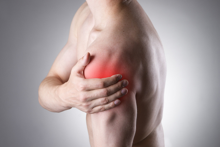 hombros: Hombre con dolor en el hombro. El dolor en el cuerpo humano sobre un fondo gris con el punto rojo Foto de archivo