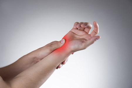 enhanced healthy: Pain in the joints of the hands. Carpal tunnel syndrome on a gray background with red dot Stock Photo