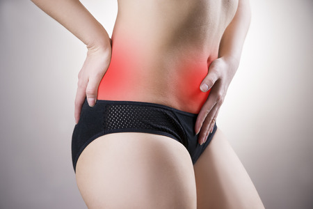 griping: Woman with abdominal and back pain. Pain in the human body on a gray background with red dot