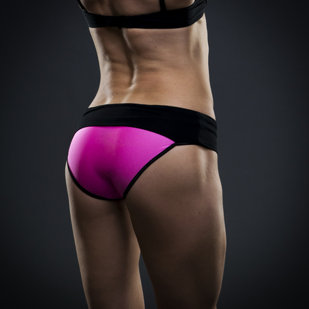 buttocks: Attractive fitness woman on gray background in studio. Muscular buttocks close-up. Trained female body