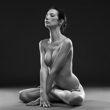 mujer desnuda sentada: Yoga desnuda. Carrocería atractiva hermosa de la mujer joven en el fondo negro