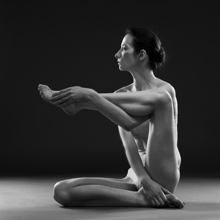 nude yoga: Nude yoga. Beautiful sexy body of young woman on black background
