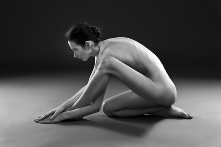 nude woman sitting: Nude yoga. Beautiful sexy body of young woman on black background