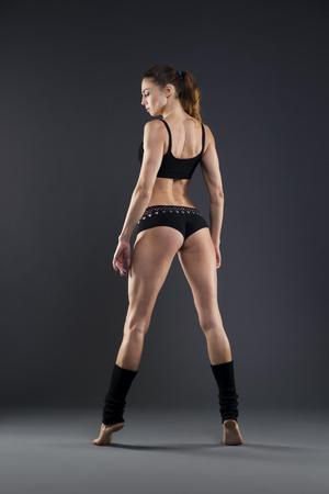 atletismo: Muscular aptitud de la mujer atractiva en el fondo gris en el estudio. Cuerpo femenino capacitado