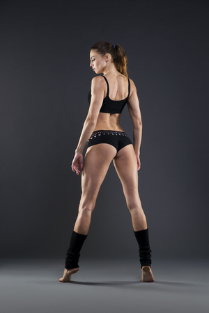 ass standing: Muscular attractive fitness woman on gray background in studio. Trained female body