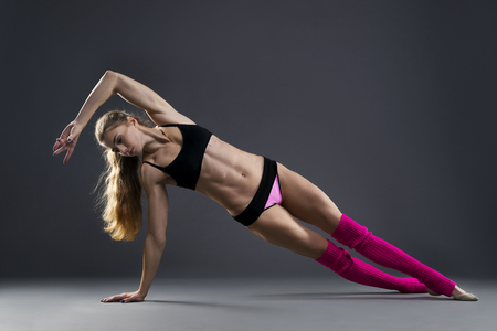 woman: Beautiful muscular woman doing exercise side plank on a gray background in studio