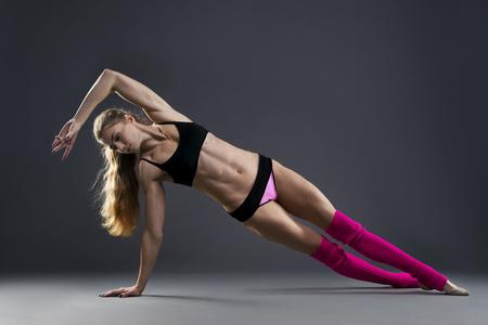 haciendo ejercicio: Mujer muscular hermosa que hace ejercicio tabla lateral sobre un fondo gris en el estudio Foto de archivo