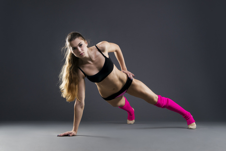 muscle woman: Beautiful muscular woman doing exercise plank on a gray background in studio
