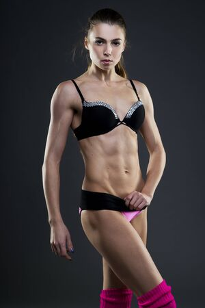 modelos negras: Muscular aptitud de la mujer atractiva en el fondo gris en el estudio. Cuerpo femenino capacitado